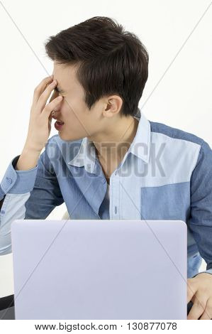 Stressed young man sitting at his desk in front of computer in office