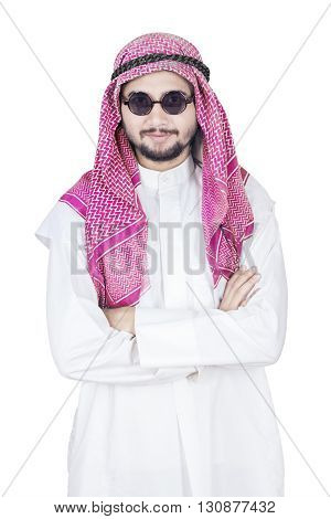 Portrait of Arabian man standing in the studio while wearing headscarf and folded hands