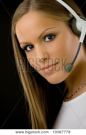 Young happy beautiful customer service operator girl in headset, smiling, isolated on black background.
