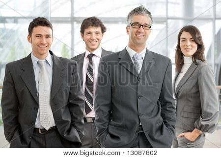 Group of four happy business people wearing gray suit, businessman leading team, smiling.