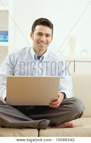 Happy young man sitting on couch and working on laptop computer at home, smiling.