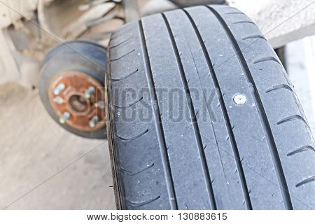 close up of screw nail puncturing car tire