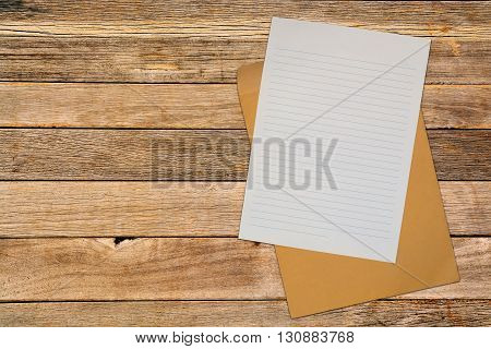 Note Paper With Brown Envelope Over Wood Blackground