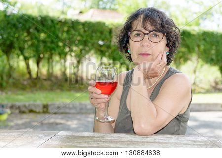 Portrait of a woman with a glass of wine in his garden