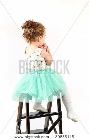 Fashion little girl in green dress in catwalk model pose stock photo.