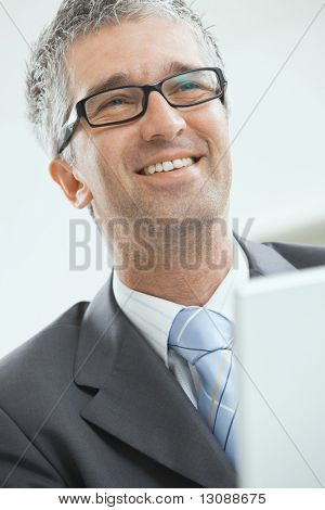 Closeup portrait of happy businessman wearing grey suit and glasses, looking at camera, smiling.