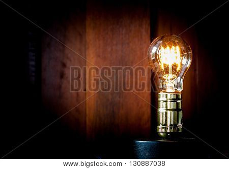 Vintage Edison light bulb illuminates on wood background.