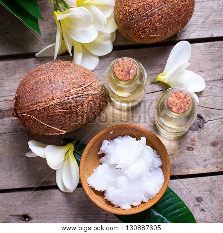 Coconuts and coconut oil on vintage wooden background. Selective focus. Flat lay. Natural organic spa products. Square image.