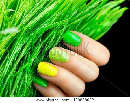 Spring manicure. Fresh Nature trendy green nails. Beautiful nail polish with grass. Green and yellow colors Eco Nail art manicure. Bottle of Nail Polish. Fashion Beauty hands. Stylish Nailpolish