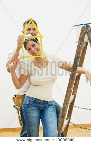 Happy young couple playing with ruler during home improvement.