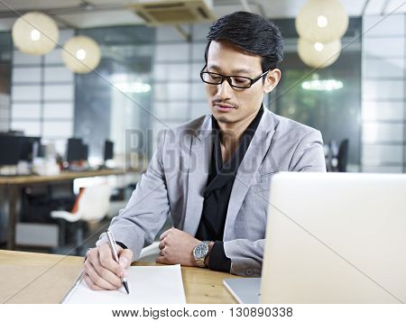 asian business man sitting at desk in office writing on a piece of paper.
