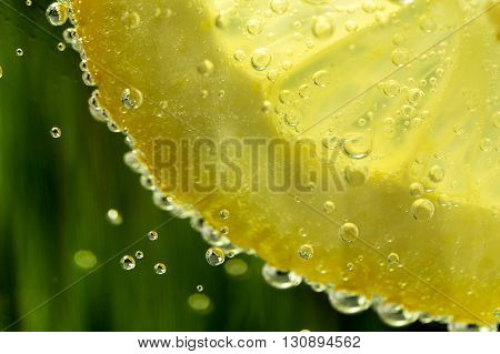 lemon in sparkle water background with sparkle water drops on glass for background or backdrop. Sparkle water background. Natural green water background. Fresh lemon juice concept.