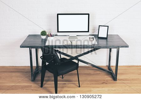Black chair next to designer table with blank computer screen frame and other items on wooden floor with white brick wall in the background. Mock up