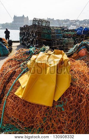 SCARBOROUGH ENGLAND - MAY 5: Trawlerman's protective oilskin smock commercial fishing nets and lobster pots in the harbour. In Scarborough England. On 5th May 2016.