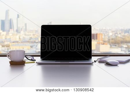 Front view of blank laptop screen coffee cup and other items on white desktop with sunlit city in the background. Mock up