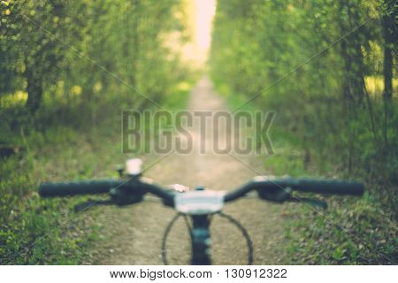 Blurred image of bike handle bar with narrow forest path and sunlight in background