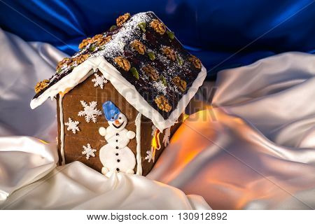 Christmas glazed gingerbread house with sugar snowman and walnuts on housetop. Against blue silk background.