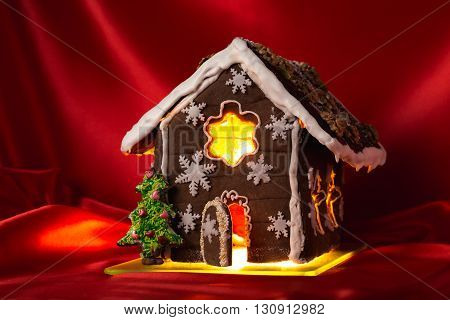 Christmas glazed gingerbread house with sweet pine and walnuts on housetop. Against red silk background.