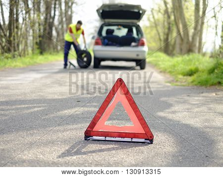 man fixing flat tire after a vehicle breakdown problem