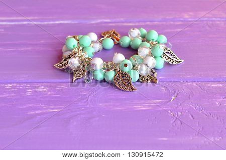 Cute charm bracelet with acrylic beads and metal pendants. Handmade beaded bracelet. Fashion women's stylish accessory. Fashionable design craft. Hand beautiful decoration. Lilac background