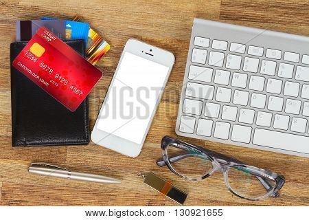desktop with mobile phone and wallet with plastic cards