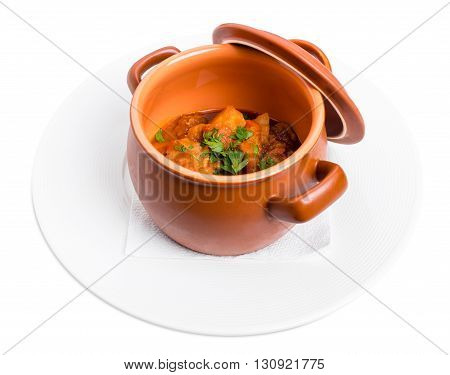 Stewed pork and potatoes covered with minced herbs in crock pot. Isolated on a white background.