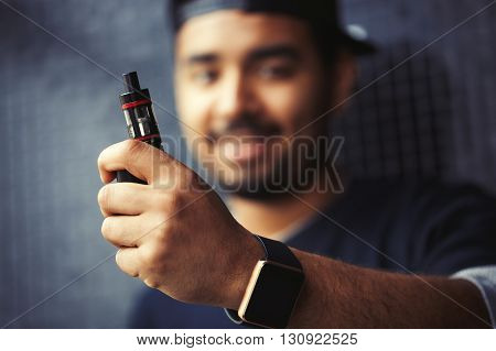 Portrait of young black man holding electronic vaporizer wearing smart wrist watches.Modern gadget that lets always stay connected to internetsocial media and trendy e-cigarette device