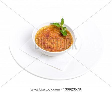 Delicious dessert cream brulee with fresh mint. Traditional french vanilla cream dessert with crunchy caramelized sugar on top. Isolated on a white background.