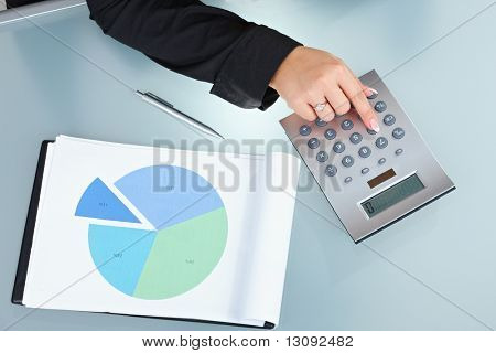 Closeup of female hand pushing key on digital calculator.
