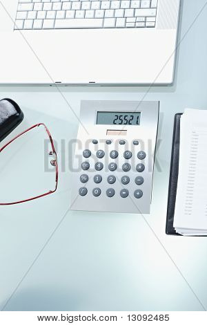 Calculator, glasses, notebook and keyboard on office desk.