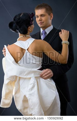 Young couple dressed in elegant clothes, cuddling, looking at each other. Woman wearing white dress, man wearing three-pieces dark suit.