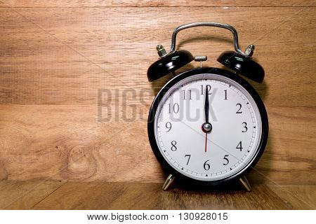 Vintage background with retro alarm clock on wood background Alarm clock shows Twelve o`clock