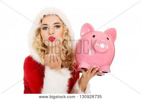 Santa woman holding a piggy bank and sending a kiss