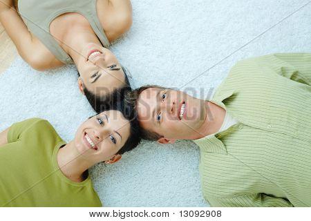 Drei Freunde auf Boden mit Köpfen nahe beieinander liegen.