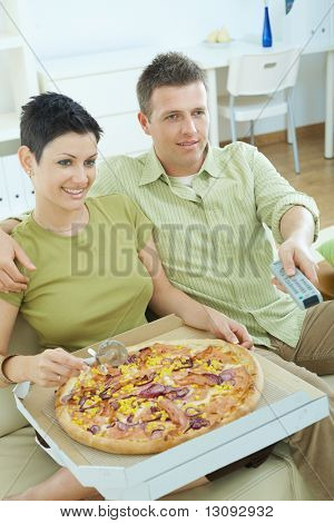 Happy couple sitting on sofa eating pizza and watching TV at home, smiling.