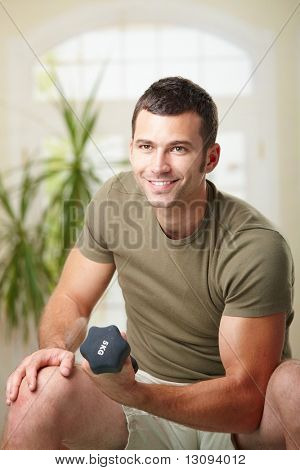 Muscular man doing biceps exercise at home with hand barbell, smiling.