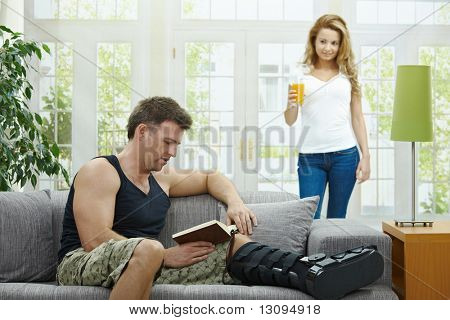 Man rasting his broken leg in cast on sofa at home, reading book. Woman bringing him orange juice.
