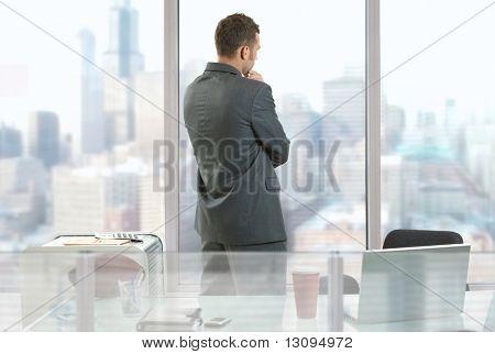 Biznesmen myślenia w biurze, patrząc z windows Vista centrum.