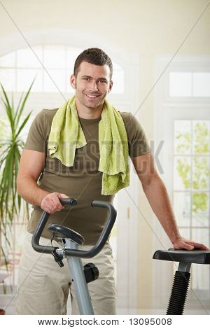 Man wearing sportswear and towel standing in living room at home with training bike, smiling.