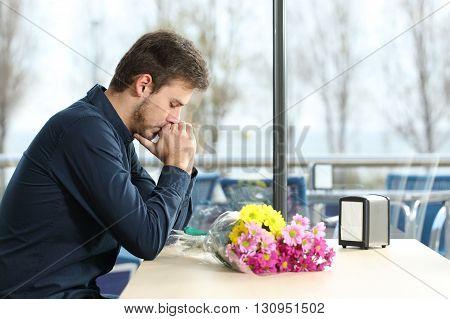 Sad man with bunch of flowers stood up in a date by his girlfriend in a coffee shop