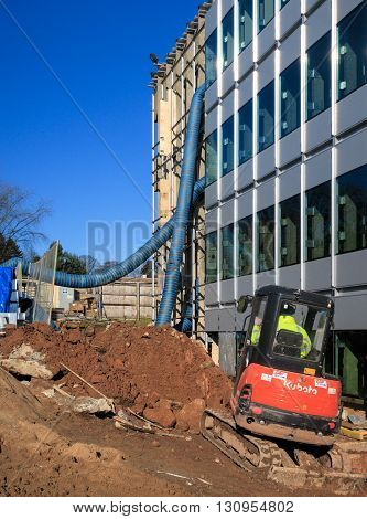 NOTTINGHAM ENGLAND - FEBRUARY 18: A male construction worker operates a mechanical digger at building works on University Of Nottingham University Park campus. In Nottingham England. On 18th February 2016.