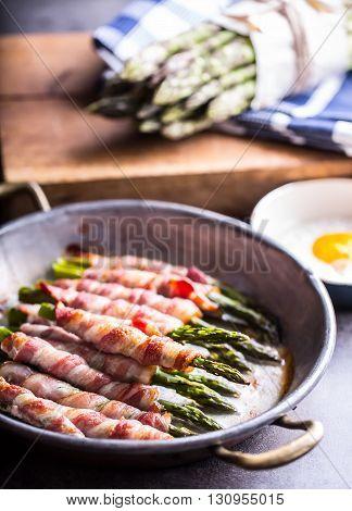 Asparagus. Asparagus and roll bacon. Grilled asparagus with rolled bacon and fried egg. Fried old pan full of rolled bacon with green asparagus and fried egg.