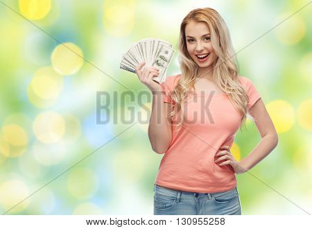 money, finances, investment, saving and people concept - happy young woman with dollar cash money over summer green lights background