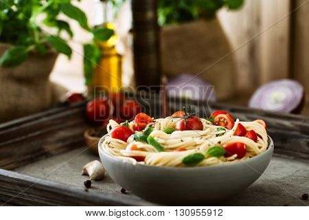 Italian cuisine. Pasta with olive oil garlic basil and tomatoes. Spaghetti with tomatoes