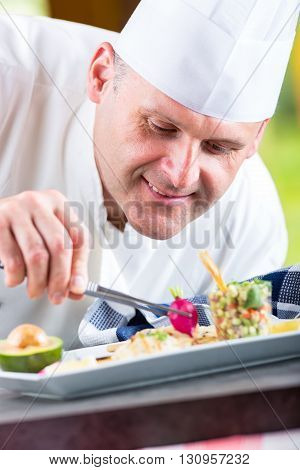 Chef. Chef cooking.Chef decorating dish. Chef preparing a meal. Chef in hotel or restaurant kitchen prepares decorating dish with tweezers. Chef cooking only hands. poster