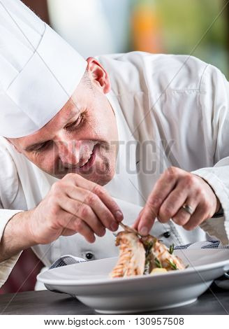 Chef. Chef cooking.Chef decorating dish. Chef preparing a meal. Chef in hotel or restaurant kitchen prepares decorating dish with tweezers. Chef cooking only hands. Decorate the rabbit thighs legs.