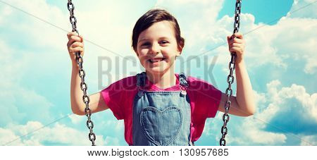 summer, childhood, leisure, friendship and people concept - happy little girl swinging on swing over blue sky and clouds background