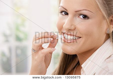 Beautiful young woman eating chewing gum, smiling.