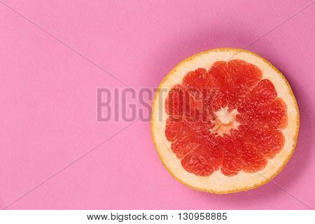 Top view of a half of fresh citrus grapefruit. Ripe juicy fruit. Juicy poster with grapefruit. Red grapefruit on a pink background. Grapefruit cut in half on pink paper texture.
