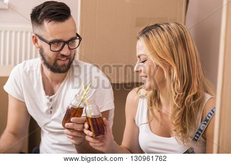 Young couple in love sitting on the floor of their new apartment surrounded with numerous cardboard boxes toasting each other for the happy beginning of their life together